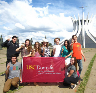 "Students from ""The Global Performance of Healing"" Problems Without Passports class in Brazil stand in front of the Metropolitan Cathedral of Our Lady of Aparecida in Brasilia, a planned city that replaced Rio de Janeiro as the capital in 1960. (Photo courtesy of Erin Moore)"