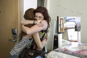 Natalie Raphael, right, hugs her new roommate on Move-in Day, Aug. 20, 2014. (Photo/David Sprague)